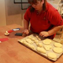 Una monitora ayuda a los niños a obrar el pan