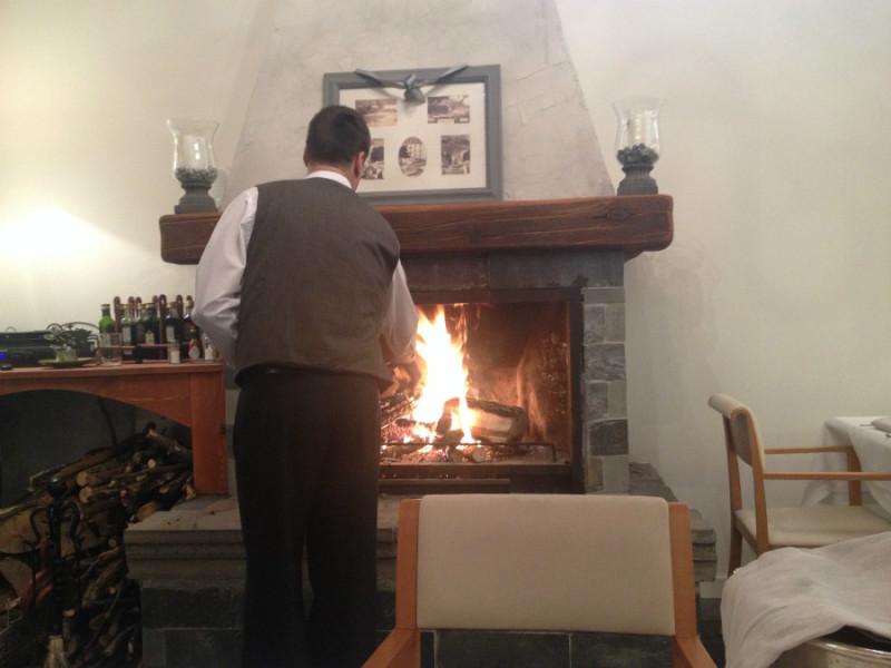 Un empleado del restaurante La Fontana atiza el fuego de la chimenea del local