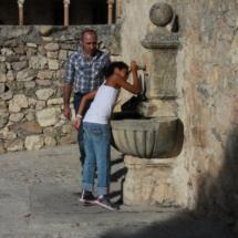 Niña bebiendo agua en una fuente de Pedraza