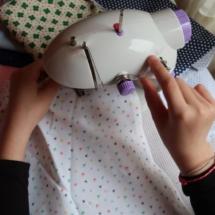 Candela practica la costura en su casa con su pequeña máquina de coser